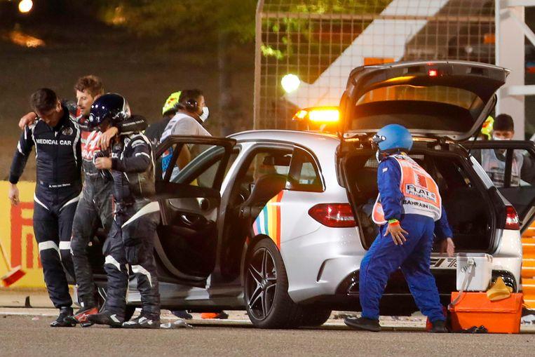 Romain Grosjean wordt door het medisch team ondersteund. Beeld AFP