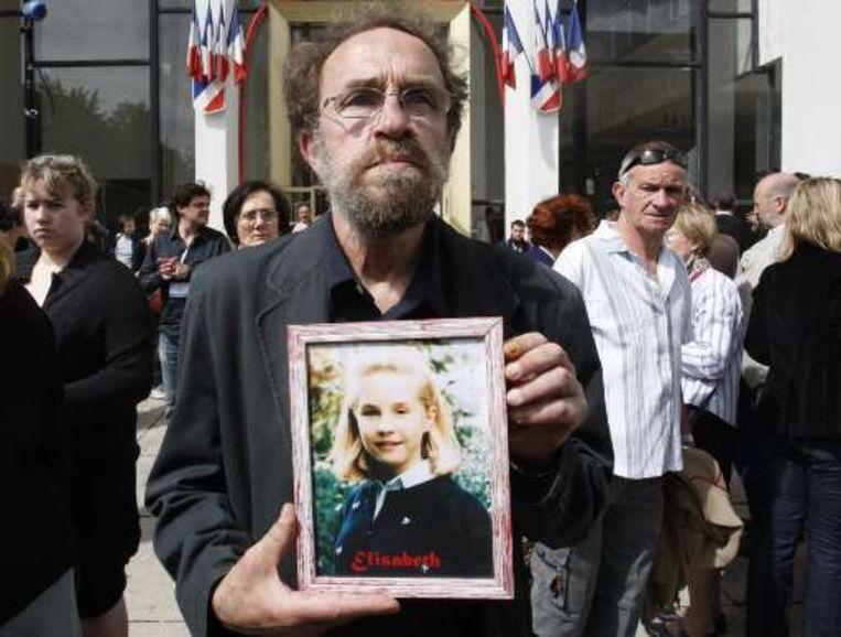 Francis Brichet met een foto van zijn vermoorde dochter Elisabeth. Beeld
