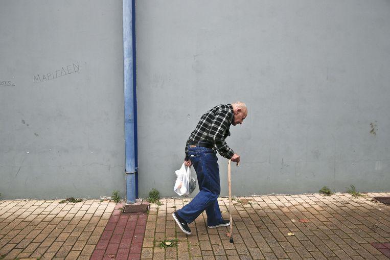 Een Griekse man met een tas eten van de daklozenzorg in Athene. Beeld null