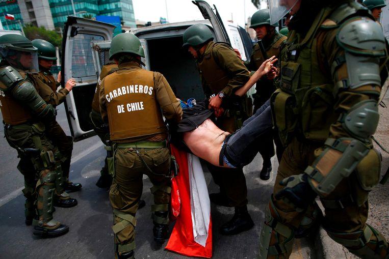 Een demonstrant wordt gearresteerd en in een  busje gegooid.