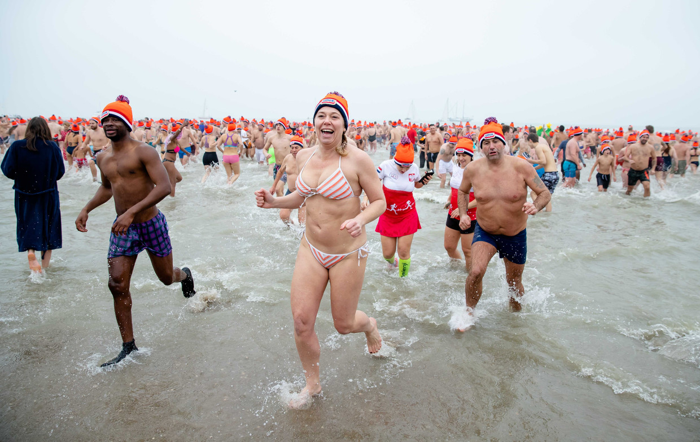Deelnemers aan de nieuwjaarsduik rennen de Noordzee.