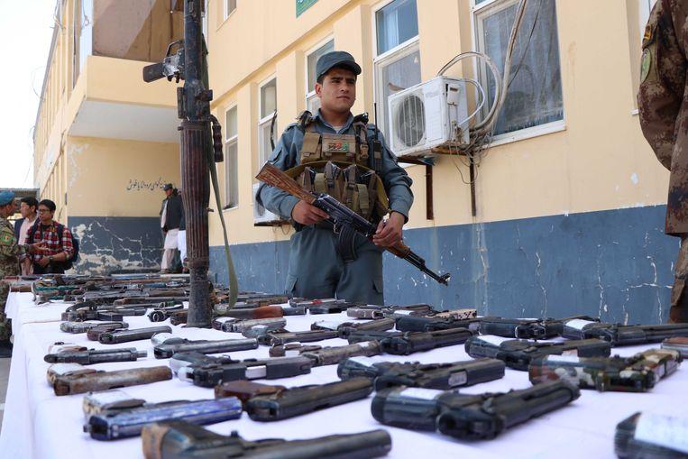 Afghaanse veiligheidstroepen bewaken ingeleverde illegale wapens in de stad Herat. Beeld EPA