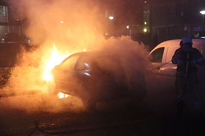Een brandweerman probeert een autobrand in Steenwijk te blussen.