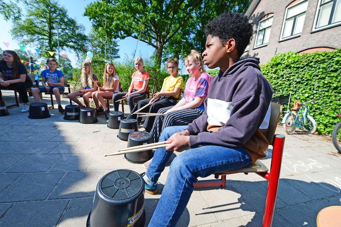 Drummen kan heel goed op een omgekeerde emmer, blijkt dinsdag als de komst van de 50e leerling op de Brookschole mert een feest voor de hele school wordt gevierd.