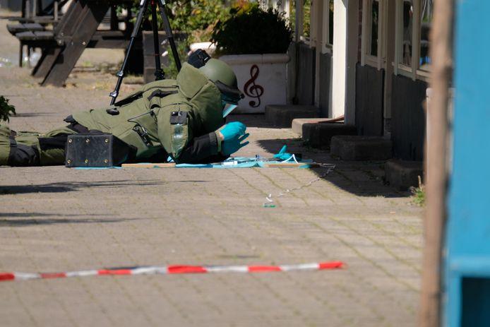 Met grote omzichtigheid is een medewerker van de Explosieven Opruimingsdienst aan het werk op de  Frits Ruysstraat, ook om sporen niet uit te wissen.