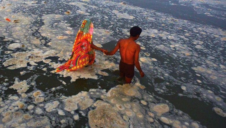 Twee vrome hindoes baden in de zwaar vervuilde, heilige rivier de Ganges om hun ziel te reinigen. Beeld afp