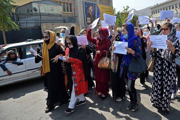 Enkele tientallen vrouwen gingen vrijdag de straat op in Kaboel om te demonstreren tegen het talibanbewind. Een talibanstrijder (links) houdt hen in de gaten.