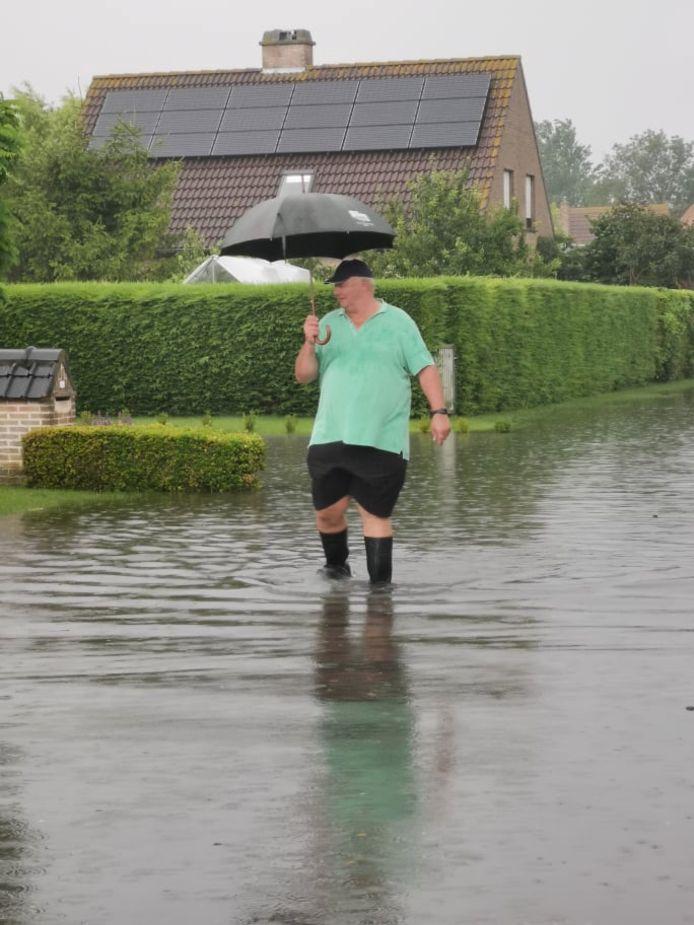 Een buurtbewoner loopt met zijn laarzen door de ondergelopen straten.