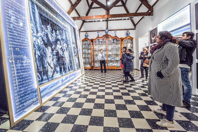 Bezoekers aan het Royal Delft Museum bewonderen een enorm Delfts blauw tableau.