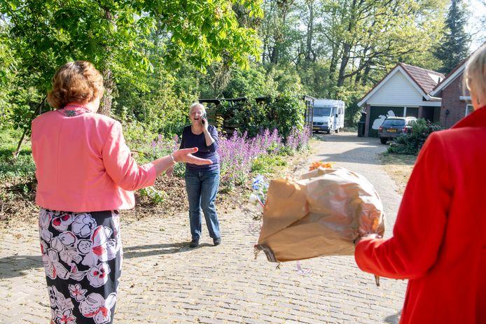 Geja Krans uit Haarle is blij verrast met het bezoek van de burgemeester. Op het lintje moet ze nog even wachten, maar ze krijgt wel alvast bloemen en taart.