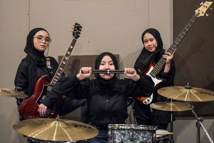 Sur cette photo prise le 8 avril 2021, les membres du groupe indonésien de heavy metal Voice of Baceprot (VOB), la guitariste et chanteuse Firda Marsya Kurnia (G), la batteuse Euis Siti Aisah (C) et la bassiste Widi Rahmawati (D) posent pour des photos après une séance d'entraînement à Jakarta. - Le groupe indonésien Voice of Baceprot, qui porte le hijab et fait du headbanging, compte parmi ses fans certaines des plus grandes stars de la musique rock, mais le groupe de heavy metal entièrement féminin a dû faire face à une bataille plus difficile pour convaincre ses parents.