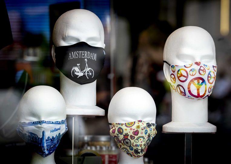 Stoffen, herbruikbare mondkapjes in een etalage in de Damstraat. De gemeente Amsterdam gaat stoffen kapjes verstrekken aan klanten van de Voedselbank. Beeld ANP