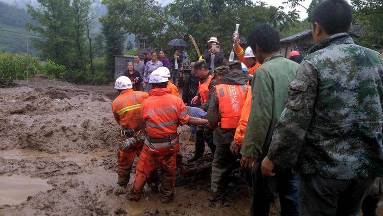 Reddingswerkers helpen overlevenden van de grondverschuiving in het Chinese dorpje Gengdi. Beeld epa