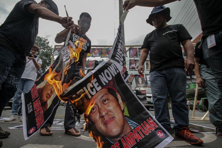 Een poster met daarop hoofdverdachte Andal Ampatuan wordt op 23 november (10 jaar na het bloedbad op Mindanao) buiten het presidentieel paleis in hoofdstad Manilla in brand gestoken.  Beeld AFP