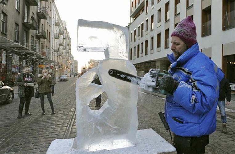 Een kunstenaar maakt een ijssculptuur in de straten van Warschau. Beeld ap