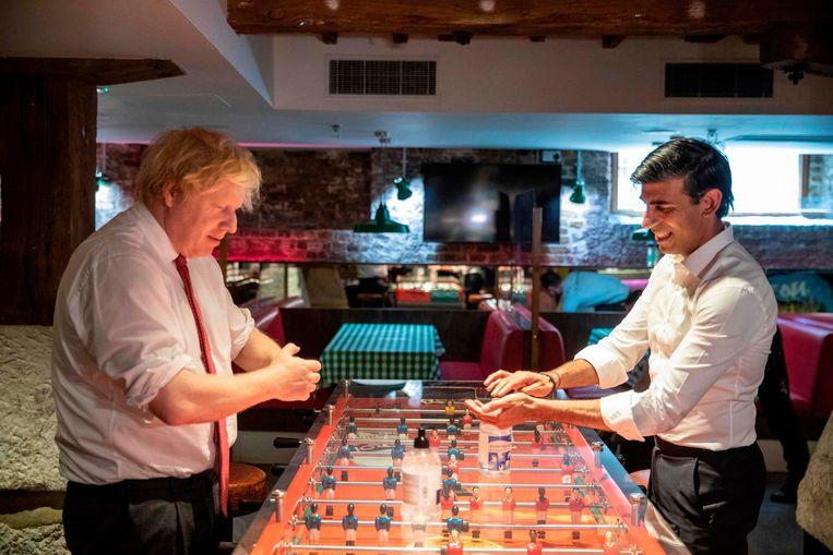 Premier Boris Johnson (l) en minister van Financiën Rishi Sunak desinfecteren hun handen voor een potje tafelvoetbal. Beeld AFP