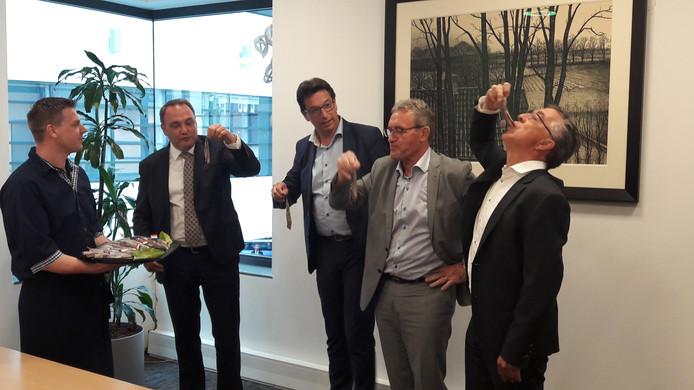 Het niet voltallige college van B en W van Rijssen-Holten liet zich dinsdagmiddag de haringen goed smaken. Vanaf links: vishandelaar Pieter Mourits, wethouders Ben Beens, Bert Tijhof en Jan Aanstoot en gemeentesecretaris Arie van Eck.