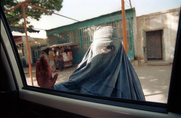 Een vrouw in boerka legt haar hand op het raam van een wagen. Beeld © Lynsey Addario / 2021 The Atlantic Monthly Group, Inc.   All rights reserved. Distributed by Tribune Content Agency