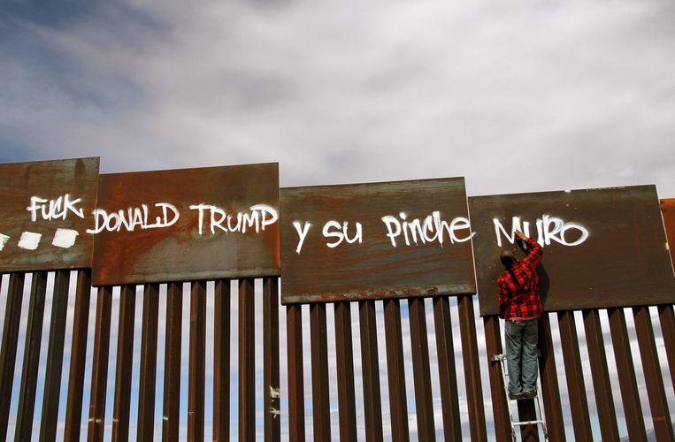 Leuzen op de muur langs  de Amerikaans-Mexicaanse grens in Ciudad Juarez in Mexico. Trump heeft ongeveer 500 kilometer van de muur gebouwd, op een totale grens van 3.200 kilometer.  Beeld AFP