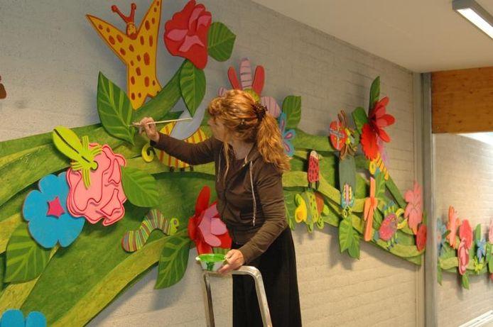Astrid van Leest aan het werk aan een groot wandvullend werk op basisschool De Klimroos in de wijk Kortendijk, waar ze lang gewoond heeft.