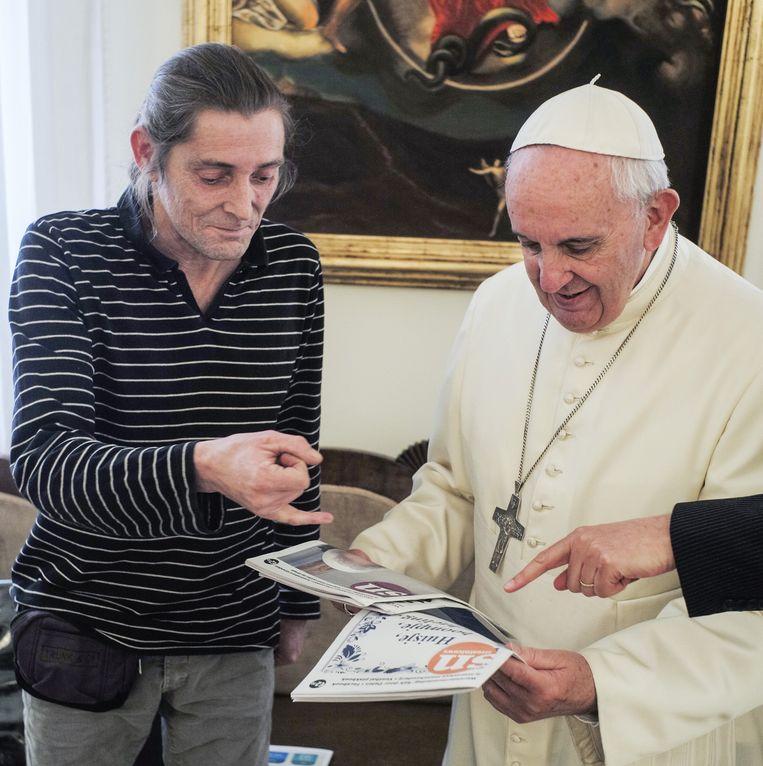 Straatnieuws-verkoper Marc geeft de paus na het gesprek wat exemplaren van de daklozenkrant. Een uitnodiging om met de Nederlandse delegatie een pizza te eten, sloeg de paus af. Beeld Straatkrant