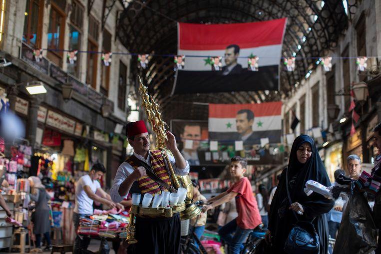 Afbeeldingen van president Bashar Assad hangen in de Hamadiyah-souk in Damascus.  Beeld AP
