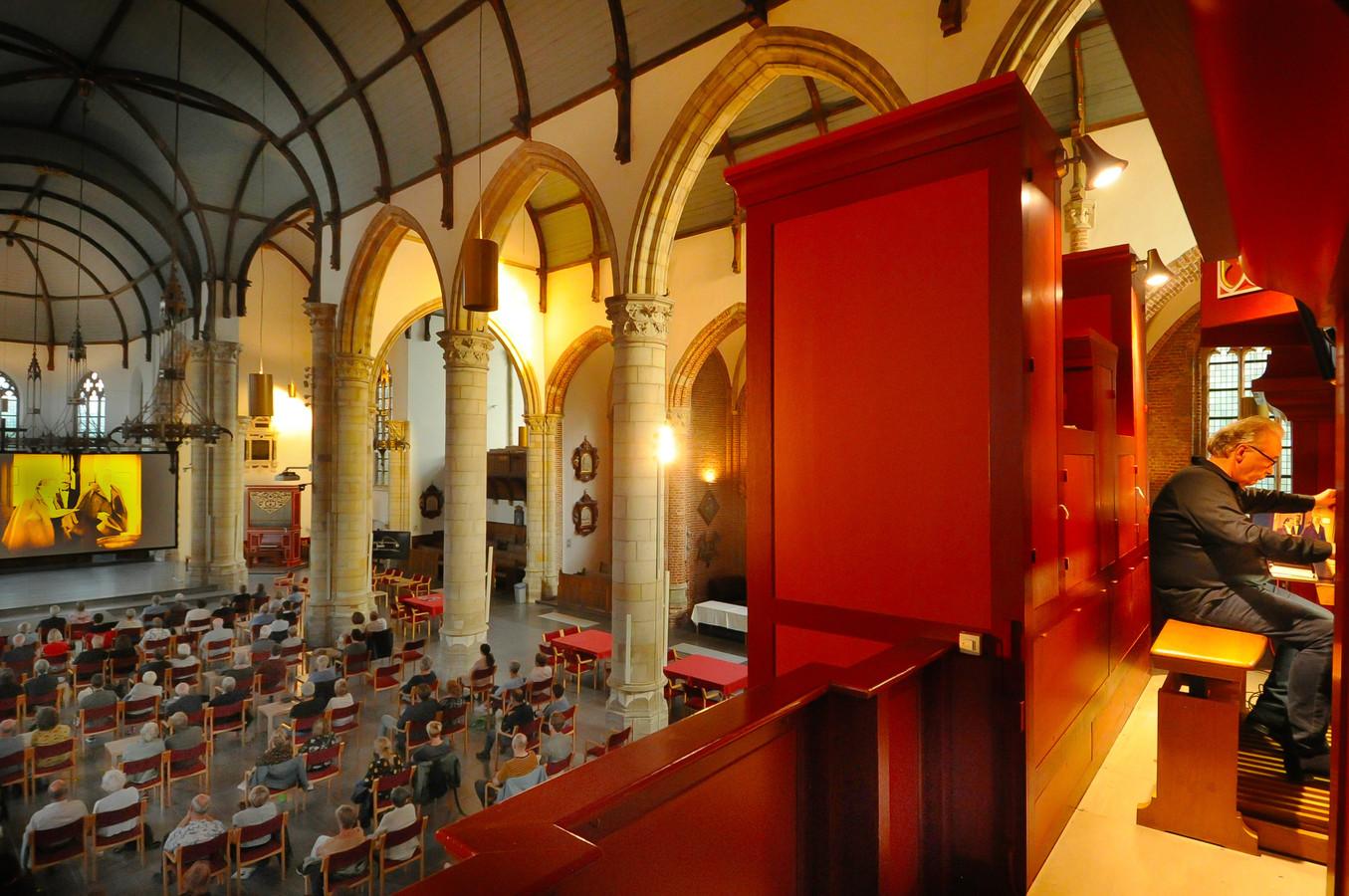 Bezoekers in de kerk zien op een groot scherm The Phantom of the Opera. Voor hen onzichtbaar zorgt organist Geert Bierling voor muzikale begeleiding.
