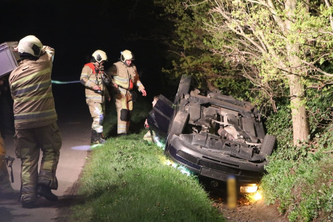 De auto ligt ondersteboven in de sloot nadat een shovel de persfotograaf opzettelijk heeft aangereden in Lunteren,