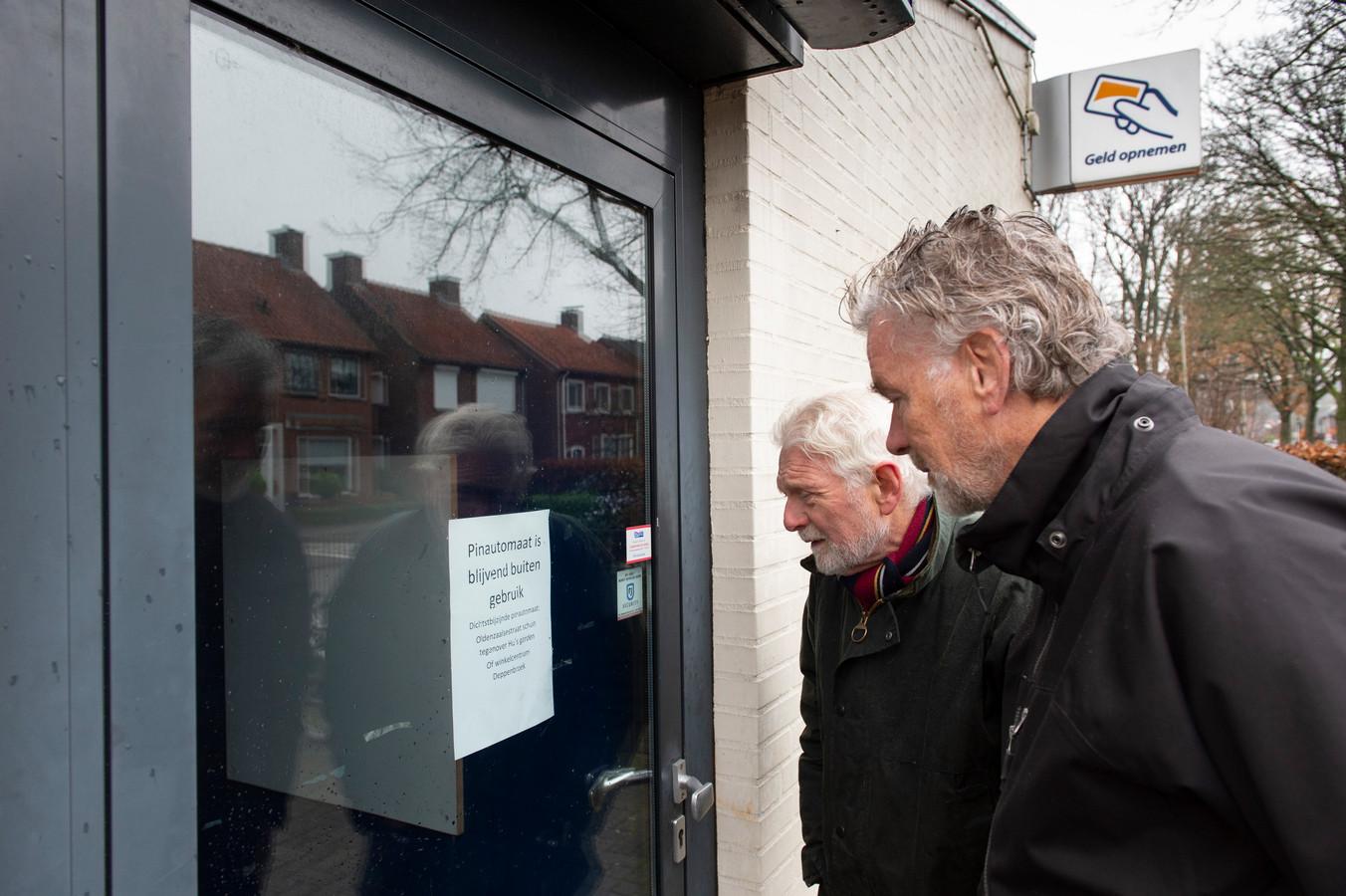 Matthie Kroezen  en Hans Strootman van de dorpsraad Lonneker bij de plotseling gesloten pinautomaat in het dorp.