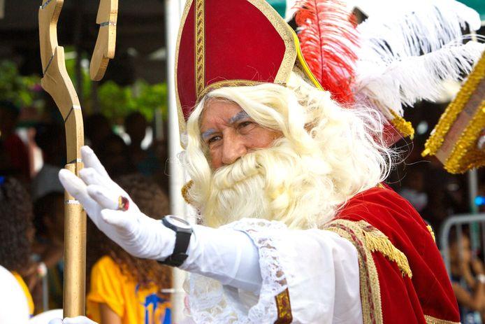 Sinterklaas zwaaiend te paard tijdens zijn intocht op Curaçao in 2016. De goedheiligman toen in Willemstad al Pieten in alle kleuren van de regenboog aan zijn zijde.