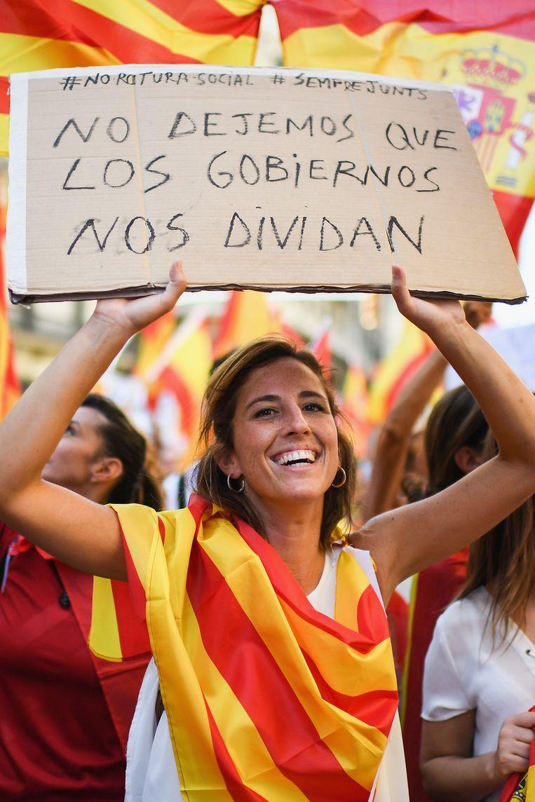 """""""We laten onze regeringen ons niet verdelen"""", staat er op het bord dat dit meisje omhoog houdt tijdens een betoging voor de eenheid van Spanje."""