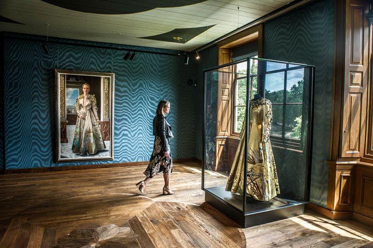 Het portret van Mathilde de Doelder gehuld in een zilverkleurige luipaardmantel van Fong Leng, met daarbij, achter glas, de goudkleurige replica. Beeld Koen Verheijden