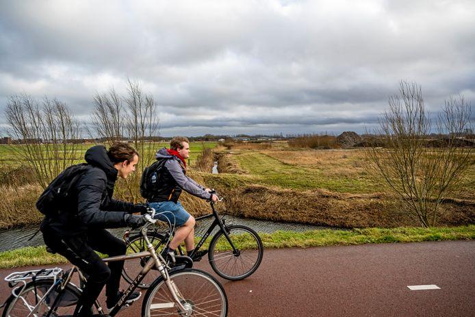 Op de weilanden naast deze fietsers wil Lansingerland de nieuwbouwwijk Wilderszijde realiseren.