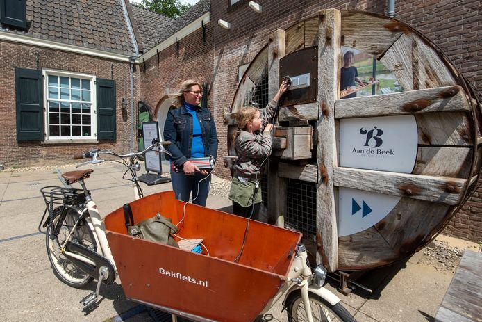 Lisa Bakker en dochtertje Hilda laden hun fiets op bij het Watermuseum. De electriciteit wordt opgewekt door een waterrad aan de achterkant van het museum.