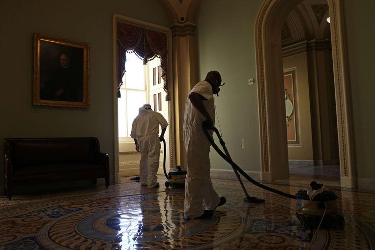 Medewerkers van het Capitool zijn een dag na de bestorming aan het werk om de boel weer schoon te maken.  Beeld AFP
