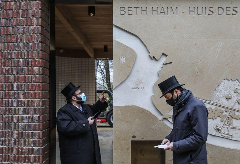 Gideon Coronel (rechts), zoon van Jacques Coronel naar wie het paviljoen is vernoemd, helpt rabbijn Joseph Serfati (links) uit Antwerpen om de mezoeza op de entree te schroeven van nieuwe het bezoekerspaviljoen op Beth Haim. Beeld Eva Plevier