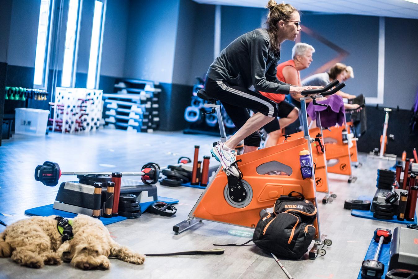 Anita Voortman is sinds tien jaar volledig blind, maar traint al jaren bij sportschool Basic Fit in Hengelo. Sinds kort doet ze ook aan spinning. Haar hulphond helpt haar naar de fiets.