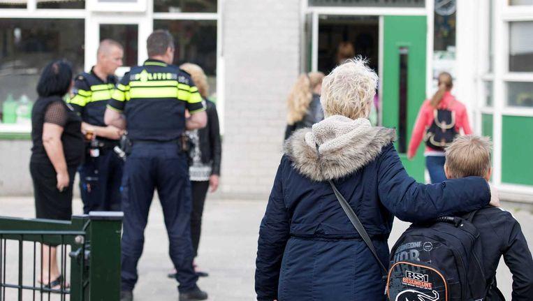 Ouders en leerlingen komen aan bij de school waar dinsdag in de buurt op brute wijze Lucas 'Puk' Boom werd geliquideerd. Beeld anp
