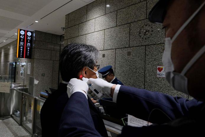 Een veiligheidsmedewerker meet de temperatuur van een bezoeker in een overheidsgebouw in Tokio.