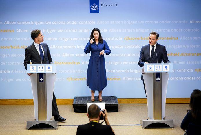 Mark Rutte en Hugo de Jonge, met in het midden tolk Irma Sluis, kondigen op 28 mei de contouren van het grote versoepelingsplan aan.