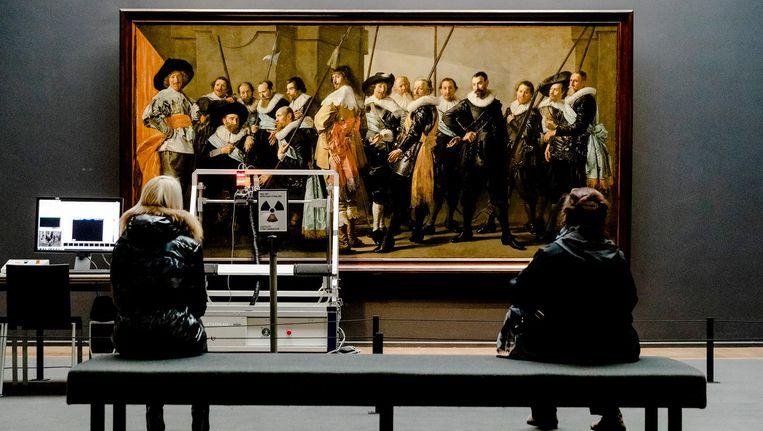 Bezoekers van het Rijksmuseum kijken toe hoe De Magere Compagnie van Frans Hals en Pieter Codde wordt gescand. Beeld anp
