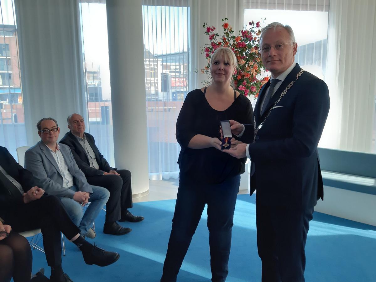 Sylvia Jannink krijgt het oorlogskruis uit handen van burgemeester Arjen Gerritsen