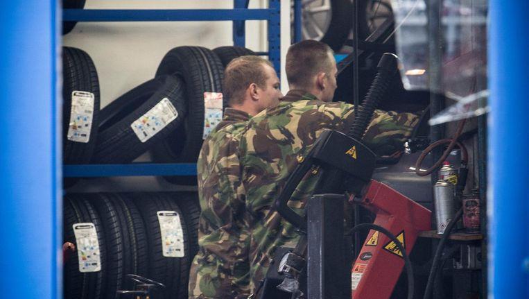 Militairen zoeken naar verborgen ruimtes bij autobandenspecialist Arob Beeld Amaury Miller