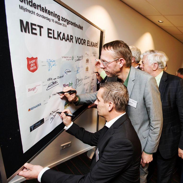 Gemeente en zorgaanbieders tekenen in Mijdrecht het contract voor de zorgcontinuïteit in een publiekscampagne na de stelselwijzigingen in de WMO en de jeugdzorg, 2014. Beeld Marlies Wessels