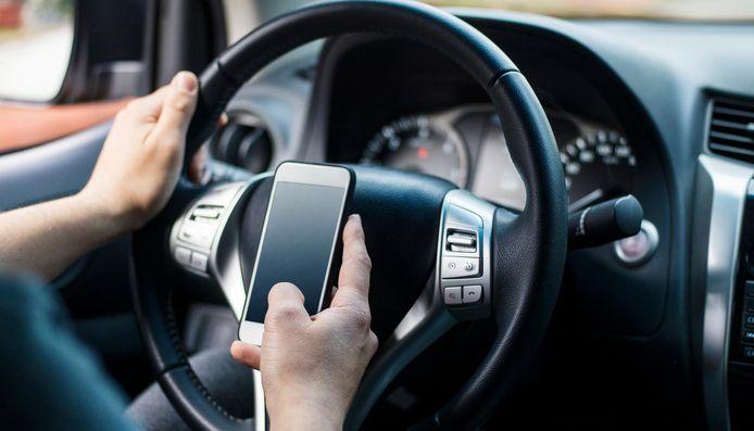 Een man op zijn smartphone in de auto.