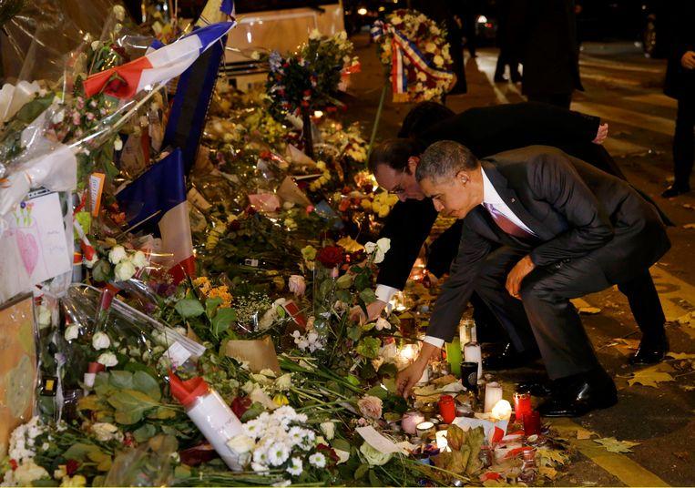 Amerikaans president Barack Obama en zijn Franse ambtsgenoot François Hollande leggen bloemen neer aan de Bataclan, vijftien dagen na de aanslagen. Beeld REUTERS