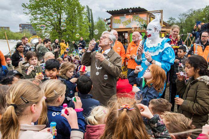 Burgemeester Charlie Aptroot blaast bellen met Zoetermeerse kinderen tijdens Koningsdag in 2019.