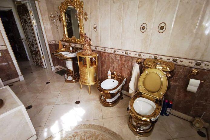 De vrijstaande villa heeft een badkamer met gouden toiletpot