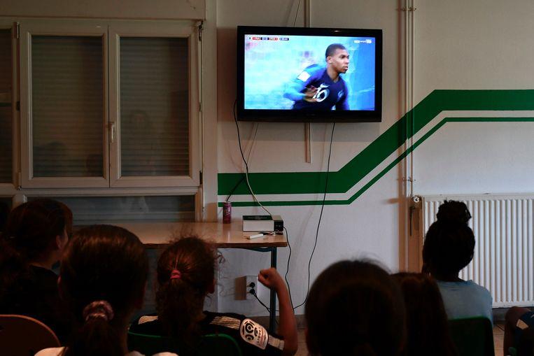 Jongeren kijken naar een wedstrijd van Frankrijk in het Leo Lagrange stadion, het stadion van Bondy. Beeld AFP