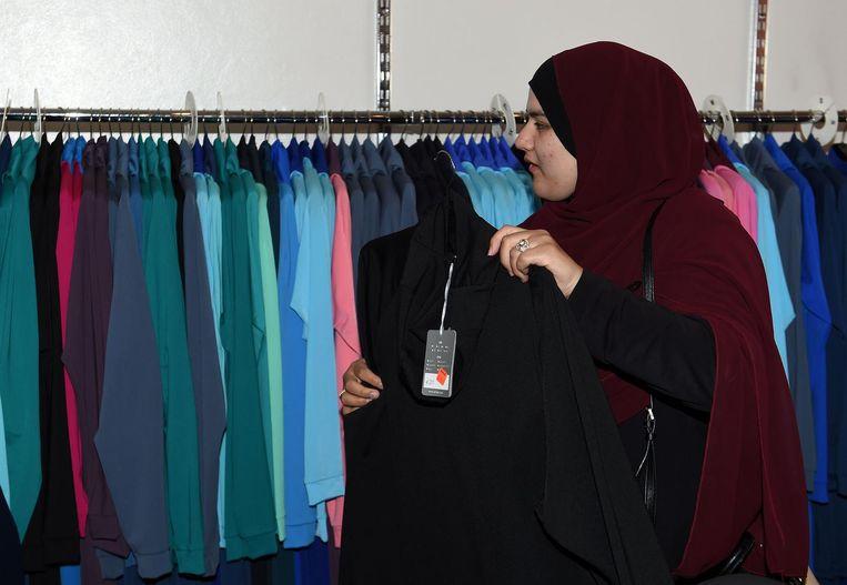 Een moslima zoekt een boerkini uit in Sydney. Beeld afp